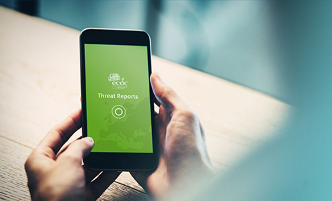Person holding a mobile device with the ECDC Threat Reports App open