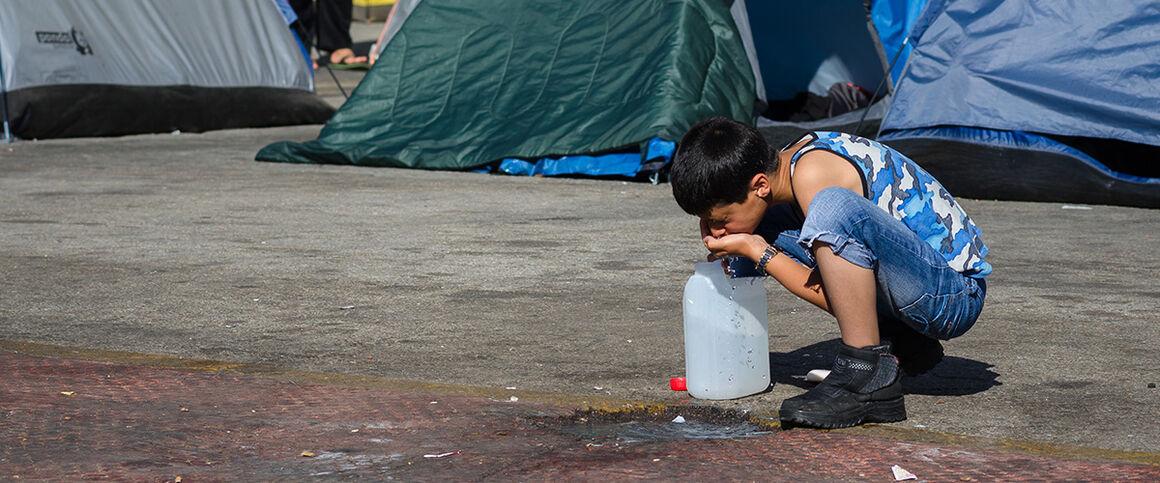Migrant child drinking water. © Istock