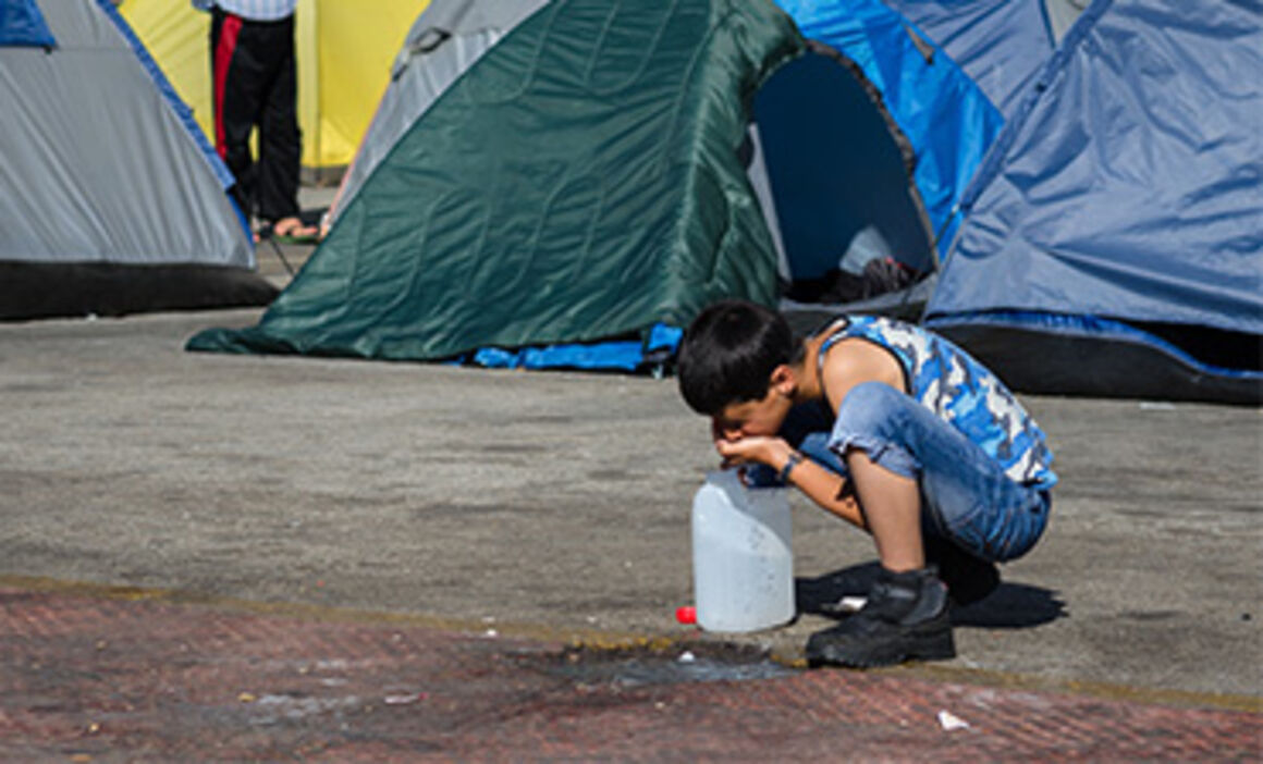 Migrant child drinking water. © Istock