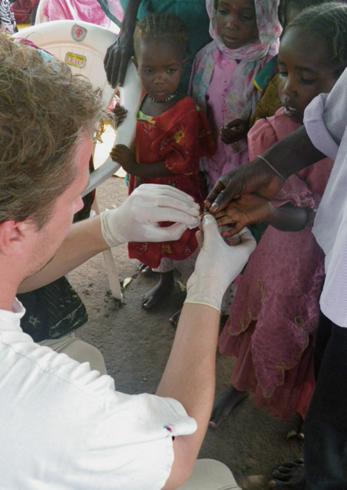 EPIET Postcard from the field -An epidemiologist taking a blood sample from a child for malaria testing, during Emergency response mission to fight malaria in Chad